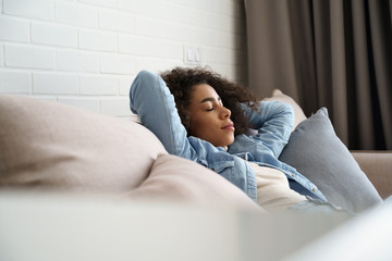 Foto auf AluDibond Entspannung Relaxed tired young african american woman napping on comfortable sofa with eyes shut closed. Calm lazy black girl leaning on couch in living room enjoying chill sleeping resting at home concept.