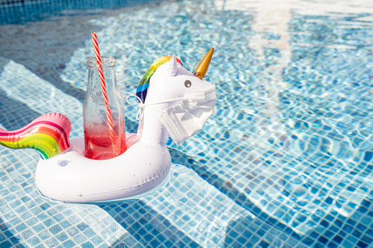 Swimming pool toy unicorn in a medical face mask. Concept of Coronavirus outbreak impact on a travel industry for summer season 2020