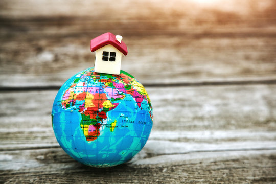 Little toy house on earth planet model. Motherland, ecology, property concept. Symbol of home
