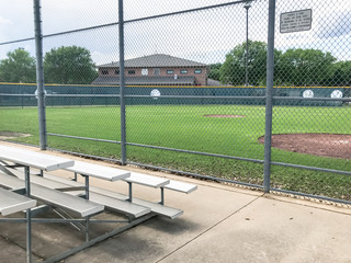 Vacant bleachers near empty baseball field with metal chain link in Dallas, Texas, USA