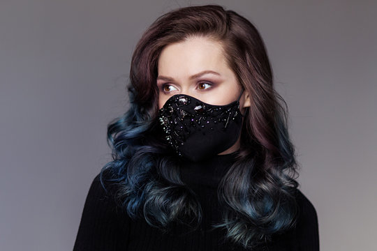 Young girl in a stylish black trendy protective mask against coronavirus portrait. Fashion luxury Quarantine Pandemic Coveid 19. Actual Accessory vogue style elegant. handmade DIY