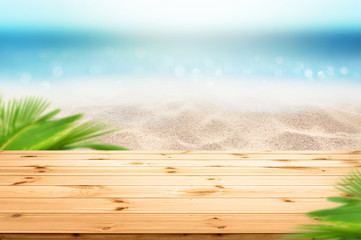 Wall Mural - Beautiful Summer background woodent table top and blur sea sandy beach view with green plam leaves as frame