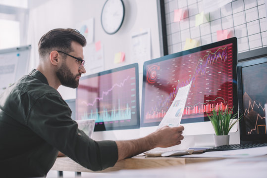 Side view of information security analyst looking at charts near graphs on computer monitors in office