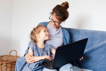 Working from home office with kid. Mother and daughter using laptop and Internet. Freelancer workplace. Happy woman teaching little child. Distance learning, isolation, homeschooling. Lifestyle moment