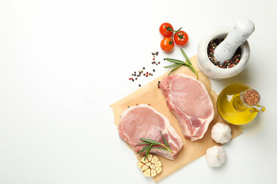Composition with raw meat and ingredients on white background, top view