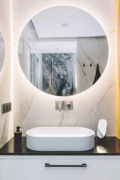Modern sink and round mirror with led light in a luxury bathroom