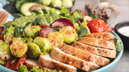 Fototapete - roasted sliced chicken fillet with brussels sprouts, tomatoes and herbs on a plate healthy nutrition