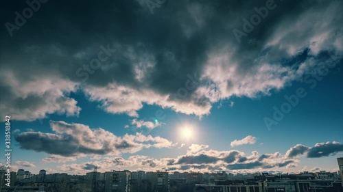 Fotobehang Dramatic clouds moving over sunset sun and blue sky background. Timelapse, 4K UHD.