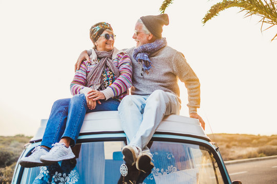 Couple of old senior traveler sit down  together on the roof of the van enjoy the sunset time together with love - forever and vacation concept for traveler retired people