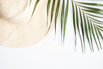 Straw beach hat with tropical palm leaf on white background. Travel, holiday, vacation concept. Flat lay, top view Fotomurales