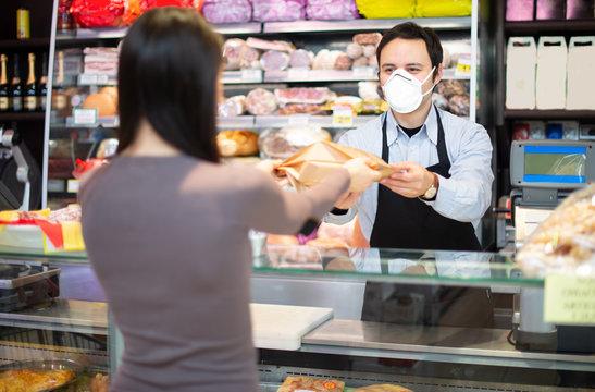 Shopkeeper serving a customer while wearing a mask