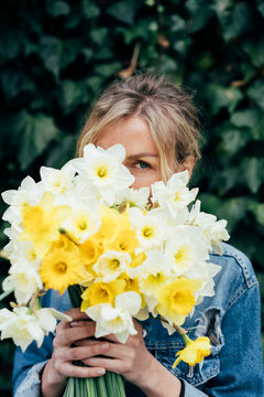 Close portrait of a woman with a bouquet of daffodils.