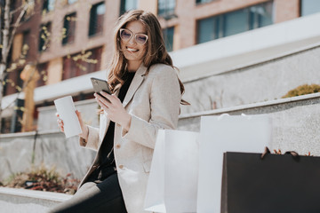 Attractive cute girl with the shopping bags and smarphone in her hand. Modern city megapolis on background. Lady making a phone call to order and shop online. Beautiful caucasian lady