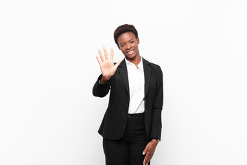 young pretty black womansmiling and looking friendly, showing number five or fifth with hand forward, counting down against white wall