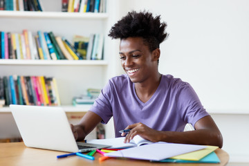 African american male young adult streaming and watching clips and movies at computer