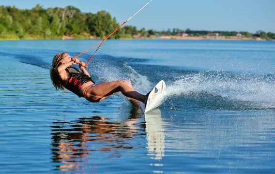 Beautiful girl wakeboarding on the shore of the river sea in the summer on a spring day in a jacket