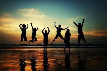 Group Of Silhouette People Jumping On Beach
