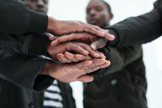 close up. a group of friends putting their hands togethe