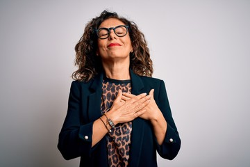 Wall Mural - Middle age brunette business woman wearing glasses standing over isolated white background smiling with hands on chest with closed eyes and grateful gesture on face. Health concept.