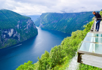 Tourist man looks at the water falling from the platform. Eagles Road viewpoint. Landscape of Geirangerfjord and Seven Sisters Waterfall in the background. Norway.