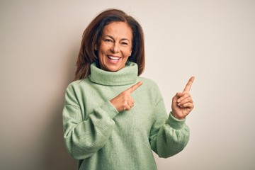 Wall Mural - Middle age beautiful woman wearing casual turtleneck sweater over isolated white background smiling and looking at the camera pointing with two hands and fingers to the side.