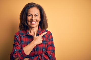 Wall Mural - Middle age beautiful woman wearing casual shirt standing over isolated yellow background cheerful with a smile on face pointing with hand and finger up to the side with happy and natural expression