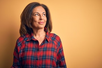 Wall Mural - Middle age beautiful woman wearing casual shirt standing over isolated yellow background smiling looking to the side and staring away thinking.