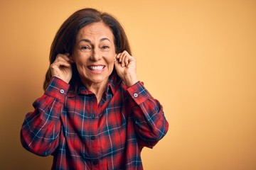 Wall Mural - Middle age beautiful woman wearing casual shirt standing over isolated yellow background Smiling pulling ears with fingers, funny gesture. Audition problem