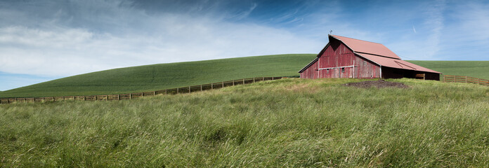 a panorama of green fields and a fence leading to an old red barn