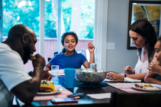 Family eating dinner together at dining room table