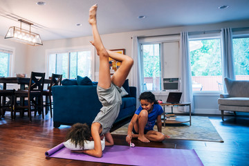 Girl doing headstand on pillow and yoga mat while sister plays in background