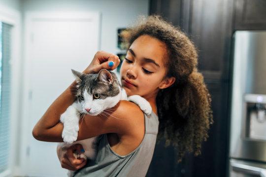 Girl hugging cat in kitchen in home