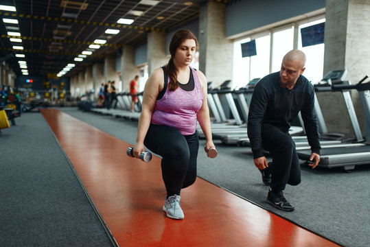 Overweight woman holds dumbbells, training in gym