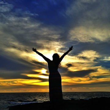 Silhouette Of Woman With Arms Outstretched Standing On Beach At Sunset