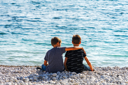 Two boys sitting on the beach, talking and throwing rocks into the sea