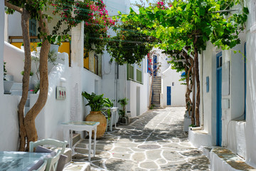 Picturesque narrow street with traditional whitewashed houses with cafe tables of Naousa town in famous tourist attraction Paros island, Greece Fototapete
