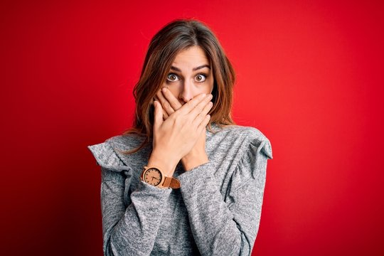 Young beautiful brunette woman wearing casual sweater standing over red background shocked covering mouth with hands for mistake. Secret concept.