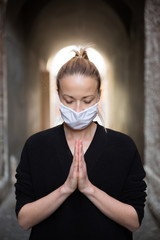 Coronavirus outbreak. Young caucasian woman wearing medical protection face mask praying over coronavirus global pandemic, for salvation of humanity, health, anxiety and depression reduction