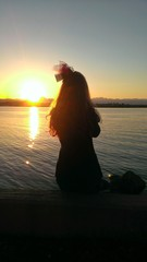 Rear View Of Teenage Girl Looking At Sea View At Sunset