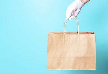 Female hand in a white glove holds brown cardboard bag on a blue background, food delivery concept.