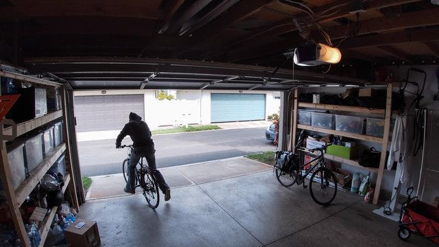 Person stealing bicycle from garage, surveillance camera view