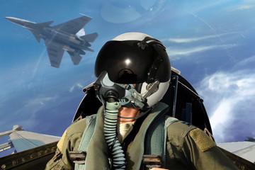 Fighter pilots cockpit view under cloudy blue sky