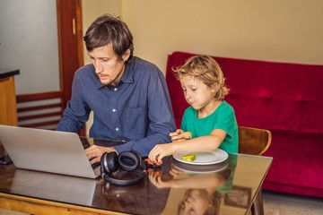 Man is trying to work from home because of the coronovirus epidemic, but his son is stopping him. Self-isolation at home. Children at home schooling. Parents at remote work. Quarantine, self-isolation
