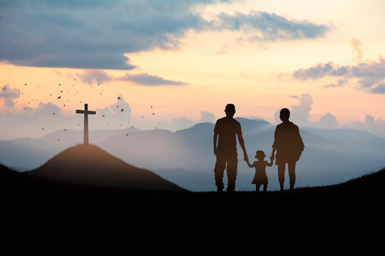 Silhouette family looking for the cross of Jesus Christ on autumn sunrise background