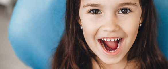 Happy caucasian girl with opened mouth smiling at camera after a teeth examination at the pediatric dentist