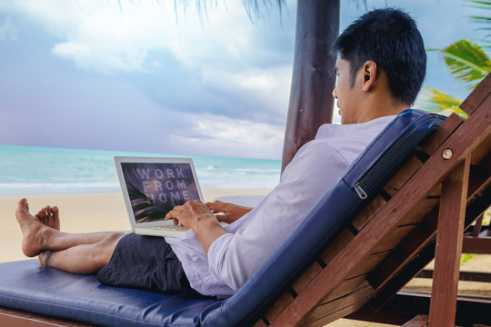 Happiness Handsome man with a shirt working with laptop sitting on the beach bed beside the sea. Working from home concept