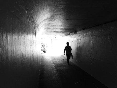 Silhouette Man Walking In Tunnel