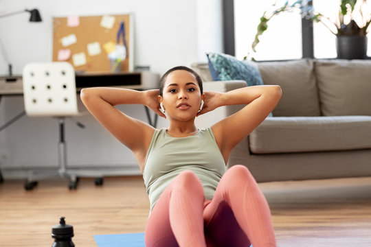 sport, fitness and healthy lifestyle concept - african american woman with wireless earphones doing abdominal exercises or sit ups at home