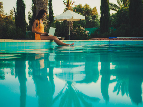 remote online working digital nomad women from the side with long hair and laptop sitting at a sunny blue water pool with plam trees in the background