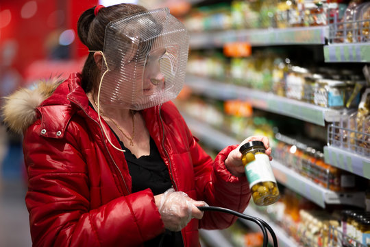 Coronovirus protection. Woman in a store with a plastic box on her face. A funny way to protect against COVID 19.Coronavirus and panic buying concept